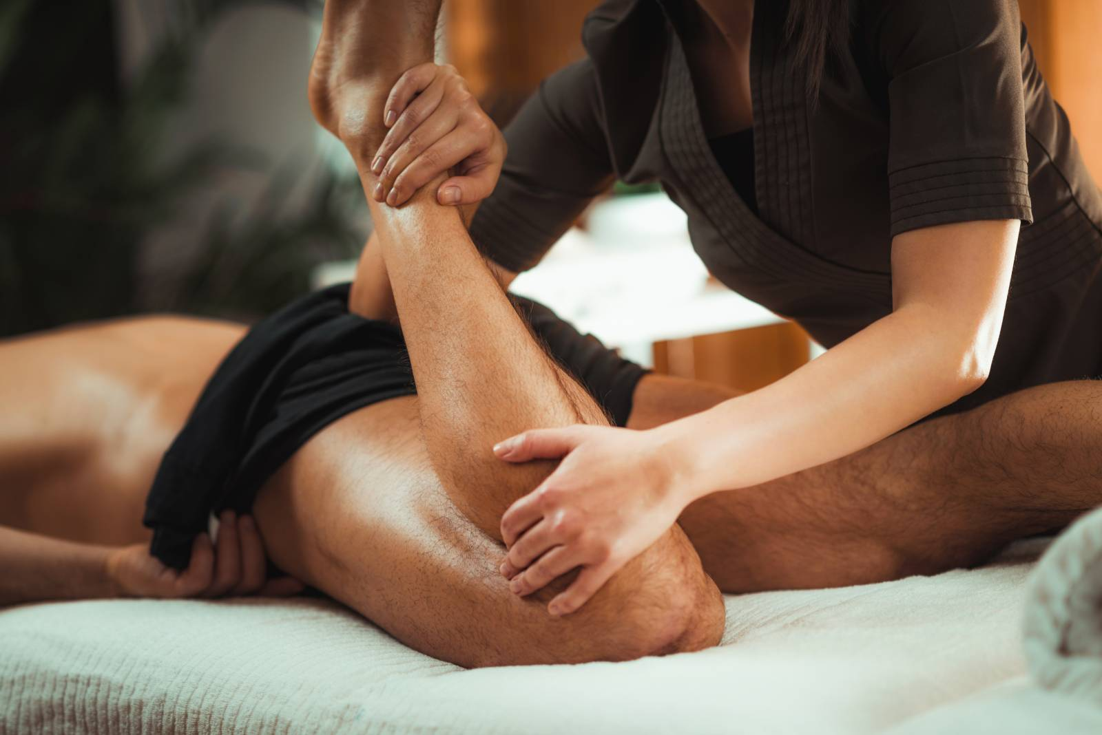 Physiotherapist massaging male patient with injured leg muscle. Sports injury treatment.